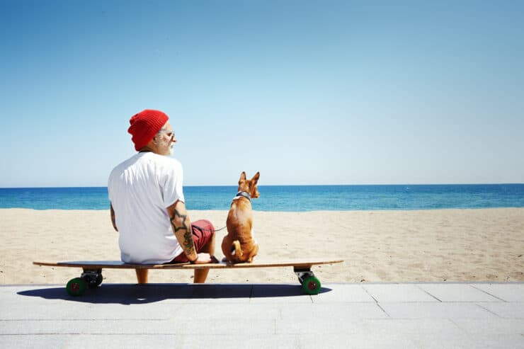 Buddy and Bello Newsletter Anmeldung Hund mit Mann auf Skateboard am Strand